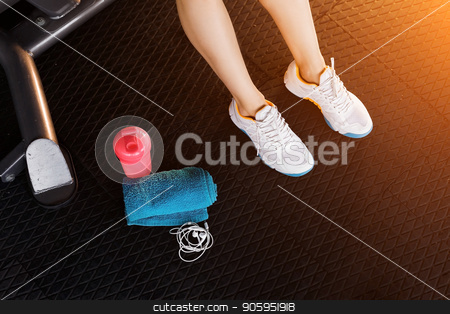 womans legs wearing sneakers in the gym stock photo, womans legs wearing white trainers siting on a mat surrounded by earphones, towel and a shaker in the gym. top view by Oleh