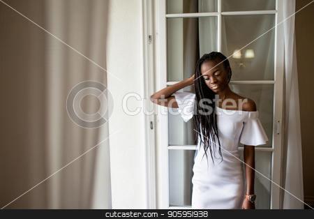 Beautiful afroamerican girl with dreadlocks or african braids in long white dress standing near the french window. stock photo, Beautiful afroamerican girl with dreadlocks or african braids in long white dress standing near the french window. by Andrii Kobryn