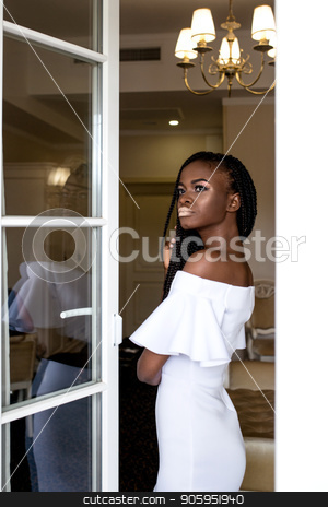 Georgeous young african american woman standing near big french window and posing for camera in a beautiful white dress. stock photo, Georgeous young african american woman standing near big french window and posing for camera in a beautiful white dress. by Andrii Kobryn