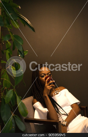 African american woman drinking wine and sitting in an armchair near the plant. Dark background. stock photo, African american woman drinking wine and sitting in an armchair near the plant. Dark background. by Andrii Kobryn