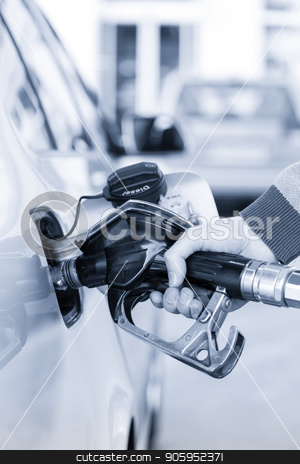 Closeup of mans hand pumping gasoline fuel in car at gas station. stock photo, Pumping gas at gas pump. Closeup of man pumping gasoline fuel in car at gas station. Greyscale blue toned image. by kasto