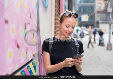 Woman using smartphone against colorful graffiti wall in New York city, USA. stock photo, Closeup of female hipster with smart phone. Woman using smartphones against colorful graffiti wall in East Village, New York city, USA. by kasto