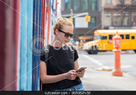 Woman using smartphones against colorful graffiti wall in New York city, USA. stock photo, Closeup of female hipster with smart phone. Woman using smartphone against colorful graffiti wall in East Village, New York city, USA. by kasto