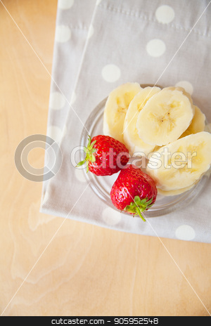 strawberry and banana on a glass plate on a wooden background stock photo, strawberry and banana on a glass plate on a wooden background. by Sergiy Artsaba