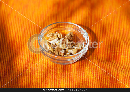 handful of walnuts in a dish on orange napkin stock photo, handful of walnuts in a dish on orange napkin. by Sergiy Artsaba