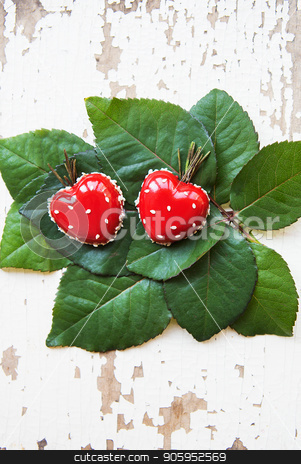 Dessert in the form of heart lies on green leaves on an old wooden background, close-up stock photo, Dessert in the form of heart lies on green leaves on an old wooden background, close-up. by Sergiy Artsaba