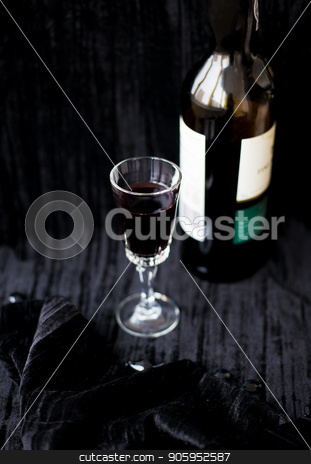 bottle and a glass of red wine on a black background. stock photo, bottle and a glass of red wine on a black background by Sergiy Artsaba