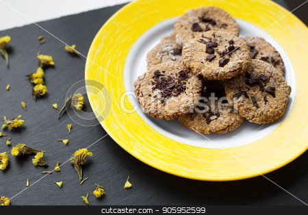 Oatmeal cookies with chocolate on bright yellow plate. stock photo, Oatmeal cookies with chocolate on bright yellow plate by Sergiy Artsaba