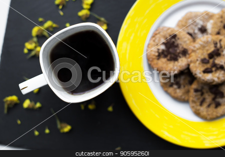 Oatmeal cookies with chocolate on bright yellow plate and cup of coffee stock photo, Oatmeal cookies with chocolate on bright yellow plate and cup of coffee. by Sergiy Artsaba