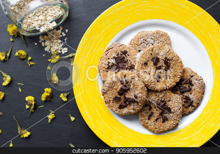 Oatmeal cookies with chocolate on a yellow plate stock photo, Oatmeal cookies with chocolate on a yellow plate. by Sergiy Artsaba