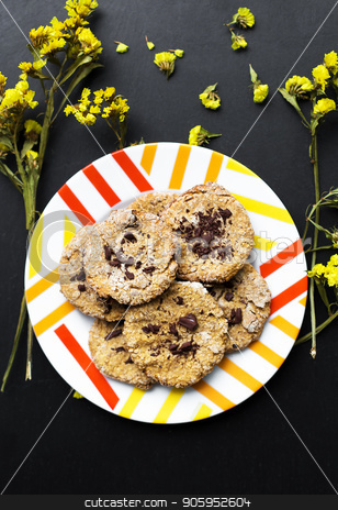 Oatmeal cookies with chocolate on a plate with bright yellow flowers stock photo, Oatmeal cookies with chocolate on a plate with bright yellow flowers. by Sergiy Artsaba