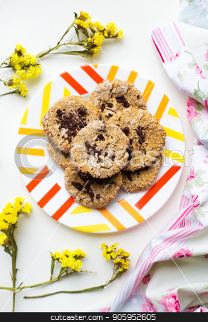 Oatmeal cookies with chocolate on a plate with bright cloth and flowers stock photo, Oatmeal cookies with chocolate on a plate with bright cloth and flowers. by Sergiy Artsaba
