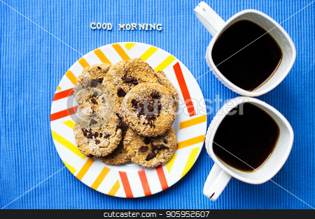 Oatmeal cookies with chocolate on blue napkin and two cups of coffee, good morning inscription stock photo, Oatmeal cookies with chocolate on blue napkin and two cups of coffee, good morning inscription. by Sergiy Artsaba