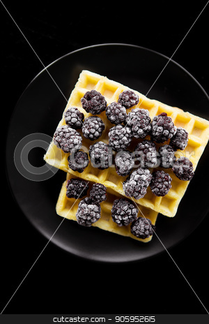 Belgian wafers with frozen blackberries on a black background, close-up stock photo, Belgian wafers with frozen blackberries on a black background, close-up. by Sergiy Artsaba