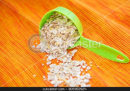oatmeal in a volumetric spoon on a napkin Orange stock photo, oatmeal in a volumetric spoon on a napkin Orange. by Sergiy Artsaba