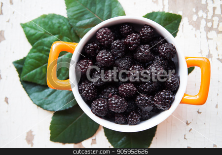 A full blackberry plate is on an old wooden background stock photo, A full blackberry plate is on an old wooden background. by Sergiy Artsaba