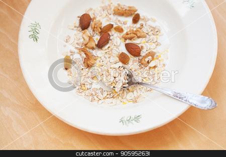 oatmeal in white bowl with nuts on orange napkin stock photo, oatmeal in white bowl with nuts on orange napkin. by Sergiy Artsaba