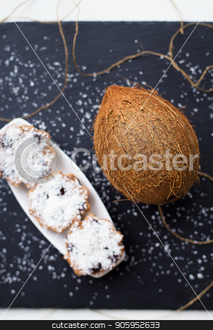 coconut muffins on a black background stock photo, Sweet coconut muffins with chocolate on a white plate. Black background by Sergiy Artsaba