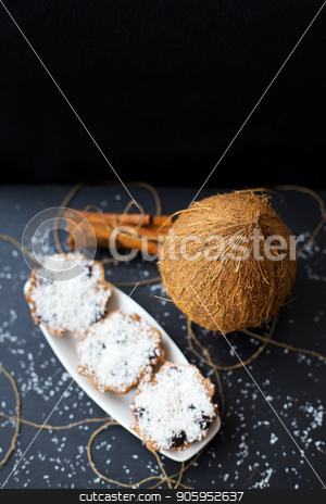 coconut muffins on a black background stock photo, coconut muffins on a white plate with whole coconut and cinnamon sticks by Sergiy Artsaba