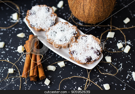 coconut muffins on a black background stock photo, coconut muffins on a black background with cinnamon sticks and whole coconut by Sergiy Artsaba