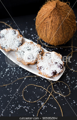 coconut muffins on a black background stock photo, coconut muffins on a white plate with a whole coconut, close up by Sergiy Artsaba