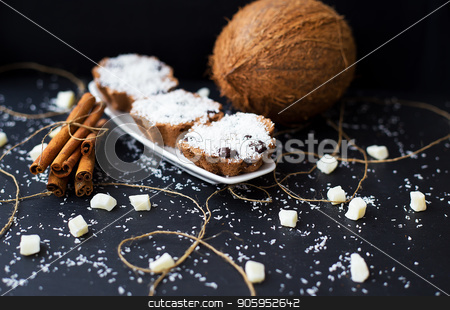 coconut muffins on a black background stock photo, coconut muffins on a black background with cinnamon sticks and whole coconut slices and candied by Sergiy Artsaba