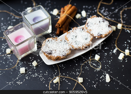 coconut muffins on a black background stock photo, coconut cupcakes and candles on a black background with cinnamon sticks and bits of candied fruit by Sergiy Artsaba