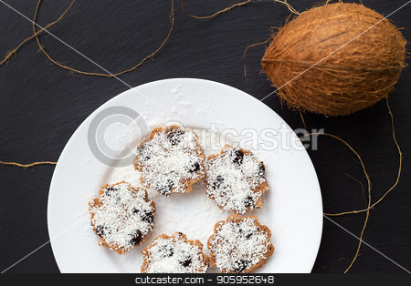 sweet coconut muffins on a white plate on a black board. stock photo, sweet coconut muffins on a white plate on a black board by Sergiy Artsaba