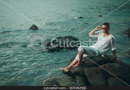 A man in a white dress and a sunglasses siiting on the rocks by the sea stock photo, A man in a white dress and a sunglasses siiting on the rocks by the sea by aaalll3110