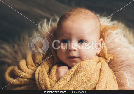newborn baby wrapped in a diaper holding a pen in the face and looking into the camera stock photo, newborn baby wrapped in a diaper holding a pen in the face and looking into the camera by aaalll3110