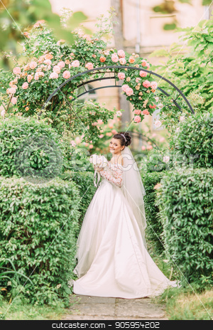 Full-length view of the smiling bride with wedding bouquet in the green garden. stock photo, Full-length view of the smiling bride with wedding bouquet in the green garden by Andrii Kobryn