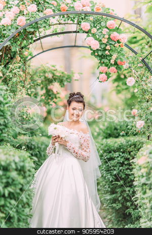 Half-length portrait of the happy bride with wedding bouquet under the arch with roses. stock photo, Half-length portrait of the happy bride with wedding bouquet under the arch with roses by Andrii Kobryn