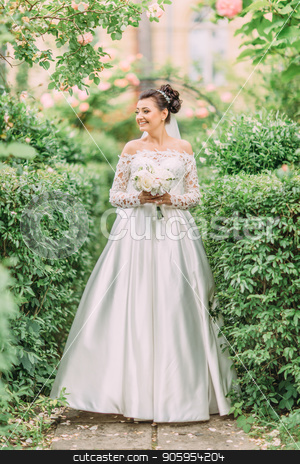 Full-length photo of the bride looking aside while spending time in the garden. stock photo, Full-length photo of the bride looking aside while spending time in the garden by Andrii Kobryn