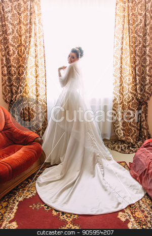 Smiling bride in the long wedding dress standing near the window. Back full-length view. stock photo, Smiling bride in the long wedding dress standing near the window. Back full-length view by Andrii Kobryn