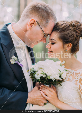 Sensitive portrait of the just married standing head-to-head while holding the wed bouquet. stock photo, Sensitive portrait of the just married standing head-to-head while holding the wed bouquet by Andrii Kobryn