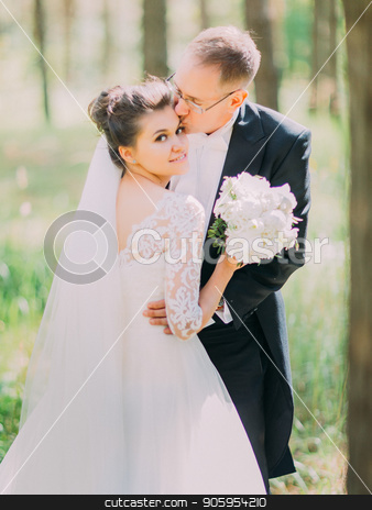 Romantic moment of the groom kissing the beautiful bride in the forehead. Forest location. stock photo, Romantic moment of the groom kissing the beautiful bride in the forehead. Forest location by Andrii Kobryn