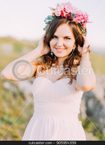 Smiling bride with the wreath of flowers on the head is touching the curly hair. stock photo, Smiling bride with the wreath of flowers on the head is touching the curly hair by Andrii Kobryn