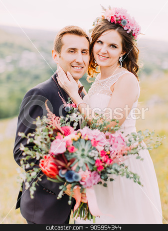 Smiling newlywed couple. The bride is stroking the cheek of the groom with the wedding bouquet. stock photo, Smiling newlywed couple. The bride is stroking the cheek of the groom with the wedding bouquet by Andrii Kobryn