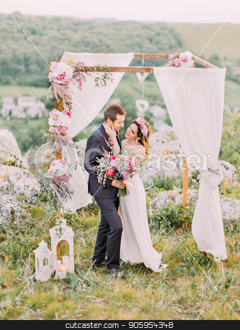 Full-length view of the bride stroking the face of the groom near the wedding arch in the mountains. stock photo, Full-length view of the bride stroking the face of the groom near the wedding arch in the mountains by Andrii Kobryn