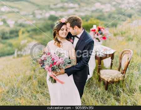 Close-up sensitive portrait of the groom hugging the bride back in the mountains. stock photo, Close-up sensitive portrait of the groom hugging the bride back in the mountains by Andrii Kobryn