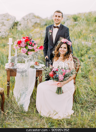 The bride with the wedding bouquet is sitting on the chair while the groom is standing behind her in the mountains. stock photo, The bride with the wedding bouquet is sitting on the chair while the groom is standing behind her in the mountains by Andrii Kobryn