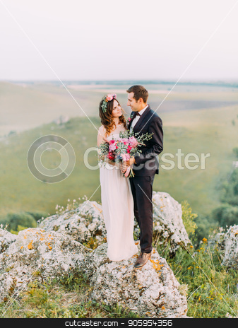 Newlywed couple is looking in the eyes of each other while standing on the rock at the background of the green mountains. stock photo, Newlywed couple is looking in the eyes of each other while standing on the rock at the background of the green mountains by Andrii Kobryn