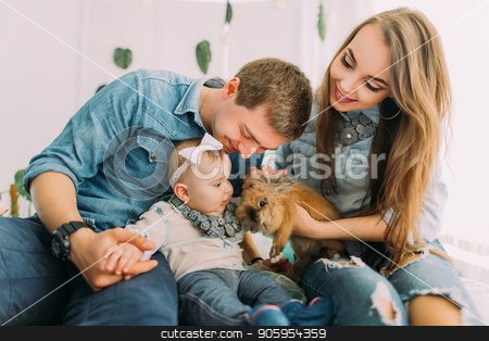 Close-up portrait of the smiling family playing with the baby and showing the little rabbit. stock photo, Close-up portrait of the smiling family playing with the baby and showing the little rabbit by Andrii Kobryn