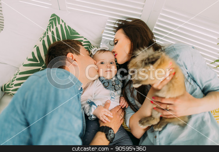 The above close-up portrait of the parents kissing their child and holding the rabbit while lying on the bed. stock photo, The above close-up portrait of the parents kissing their child and holding the rabbit while lying on the bed by Andrii Kobryn
