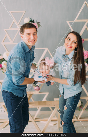 The vertical photo of the smiling family swining the little baby in their hands at home. stock photo, The vertical photo of the smiling family swining the little baby in their hands at home by Andrii Kobryn