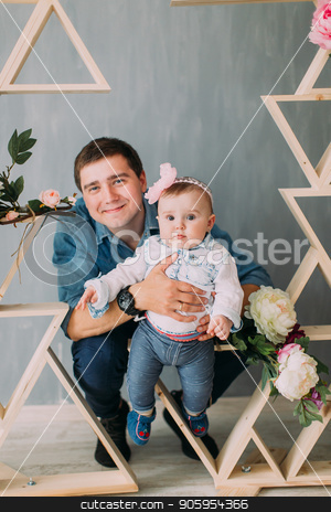 The smiling father is holding the toddle behind the wooden decorations.