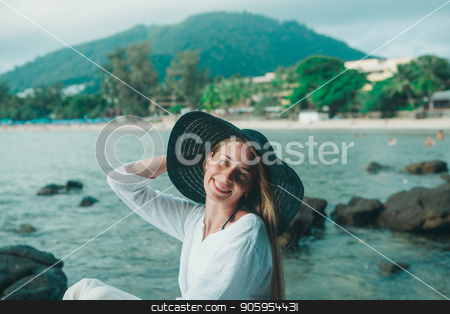 handsome girl in hat on the beach background. Portrait of a woman in white clothes and balck hat on the sea stock photo, handsome girl in hat on the beach background. Portrait of a woman in white clothes and balck hat on the sea by aaalll3110