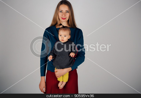 family photo: a woman holding a child in her arms. Fashion for the whole family: mother and daughter dressed in yellow, gray, red. Model shows clothes stock photo, family photo: a woman holding a child in her arms. Fashion for the whole family: mother and daughter dressed in yellow-gray. Model shows clothes by aaalll3110