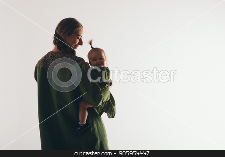 family photo: a woman holding a child in her arms. Fashion for the whole family: mother and daughter dressed in green. Model shows clothes stock photo, family photo: a woman holding a child in her arms. Fashion for the whole family: mother and daughter dressed in green. Model shows clothes by aaalll3110