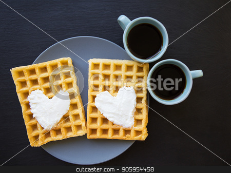Delicious Belgian waffles with cream on a black background and two cups of coffee. stock photo, Delicious Belgian waffles with cream on a black background and two cups of coffee by Sergiy Artsaba